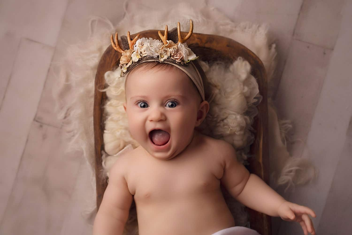 Adorable baby girl wearing antlers for Christmas by Annie Whitaker Photography