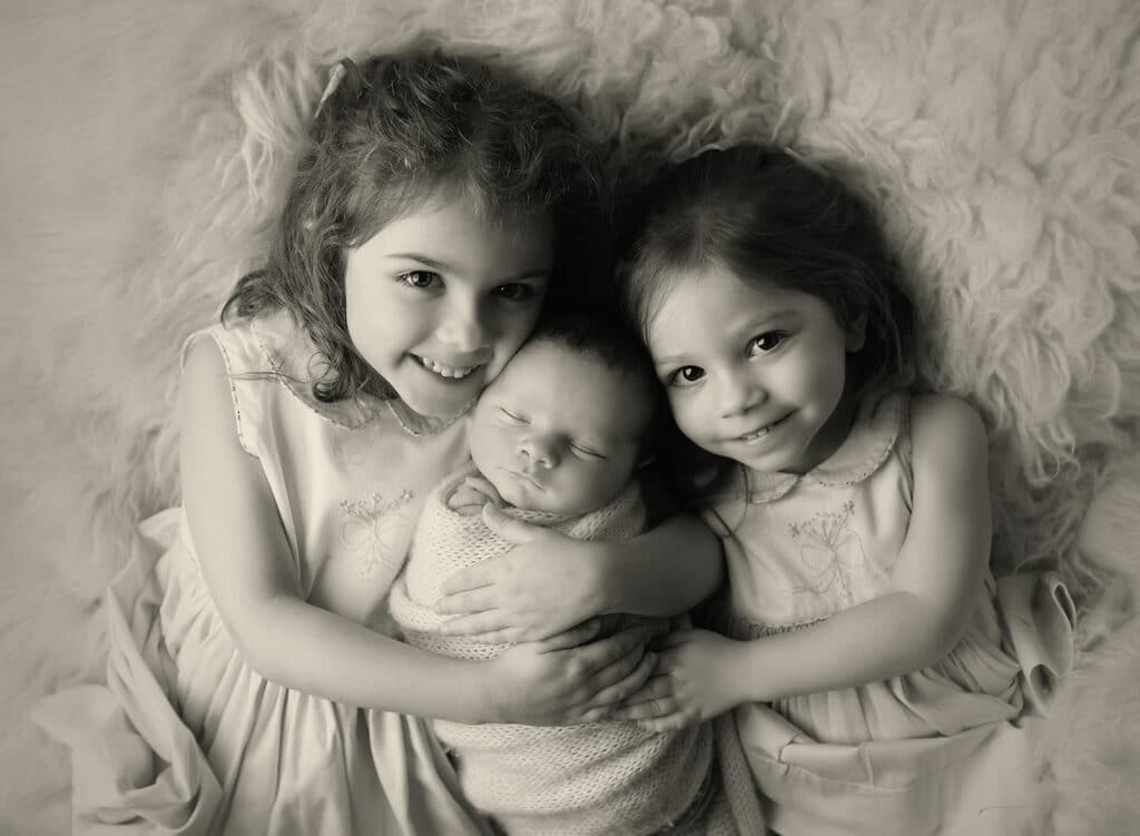 two big sisters with newborn brother