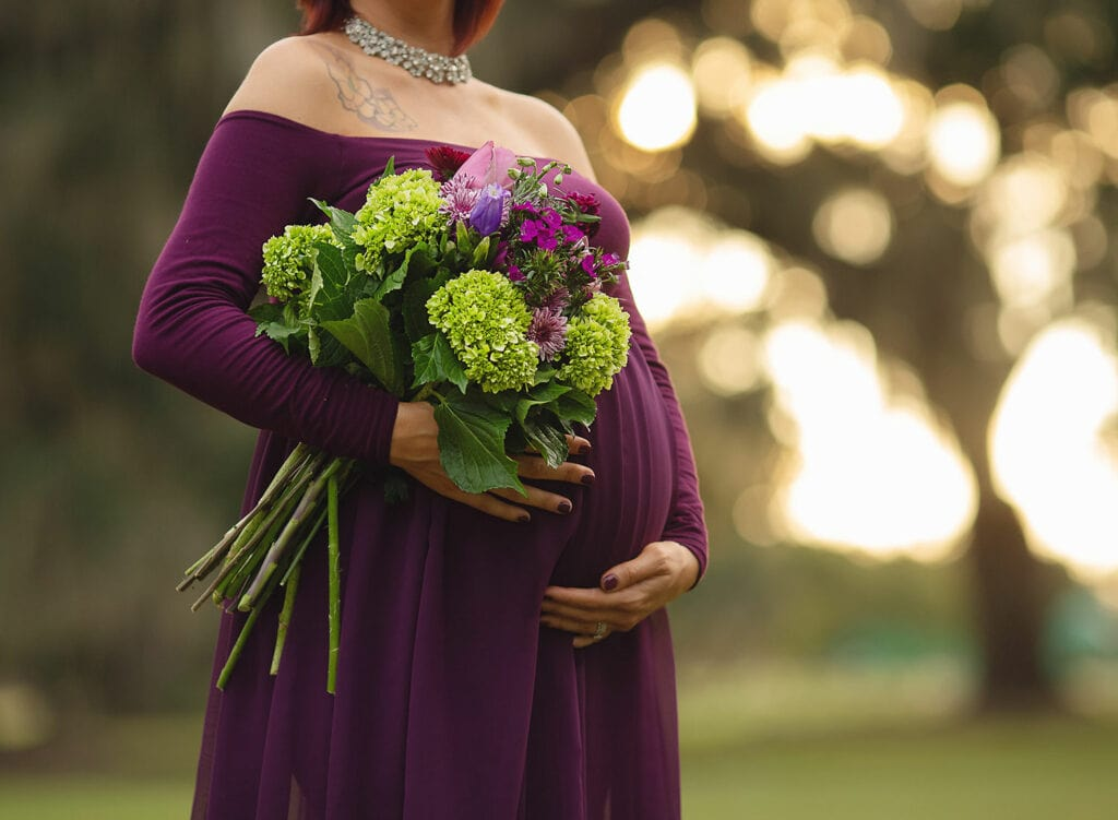 mother to be holding bundle of flowers