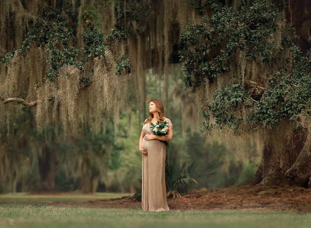 mother to be holding flower bouquet under large oak tree in Mandeville