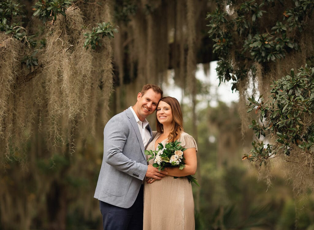 expecting couple with flower bouquet under large oak tree