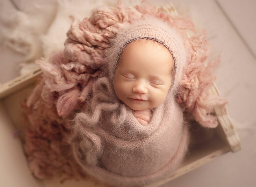 newborn girl in pink wrap and bonnet smiling