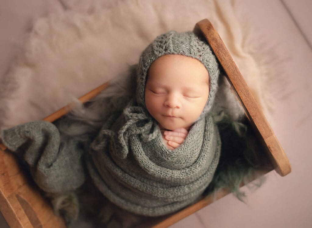 newborn swaddled in tiny bed