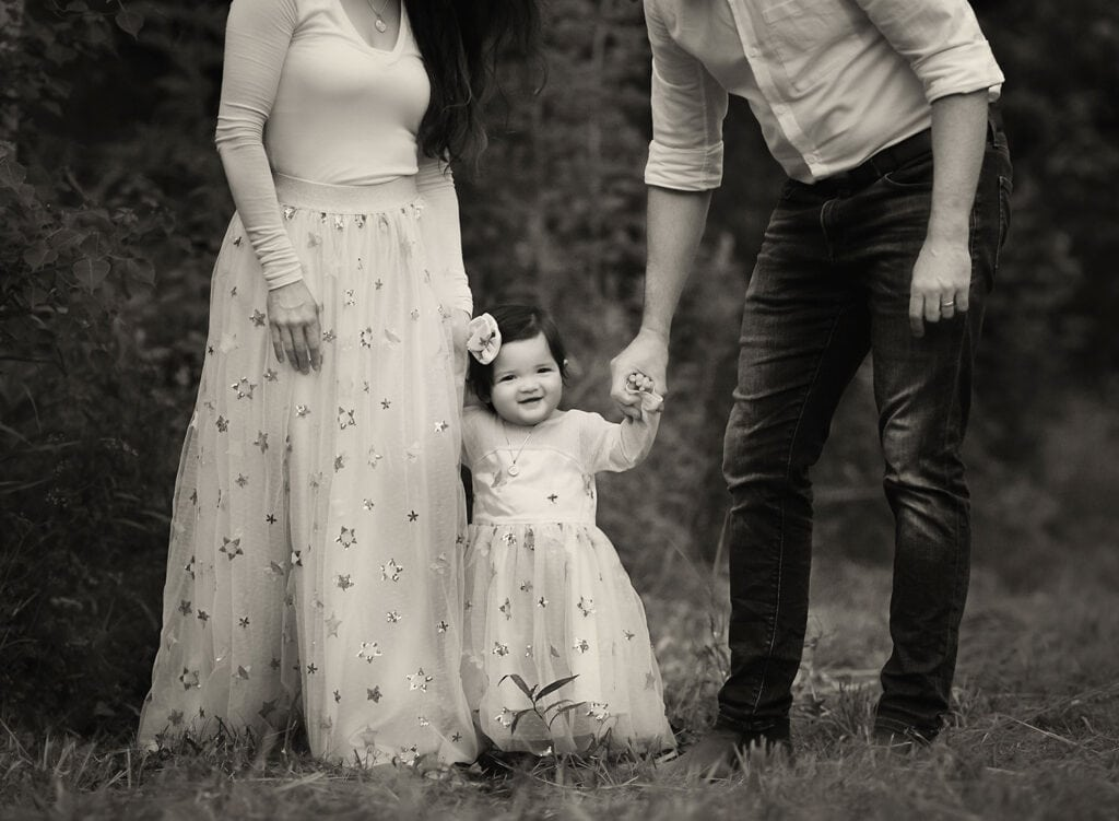 black and white photo of baby holding mom and dad's hands