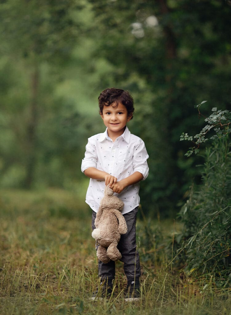 little boy holding bunny toy
