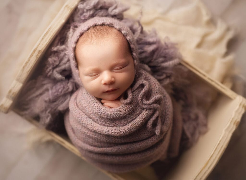 perfect newborn wrapped in purple knits