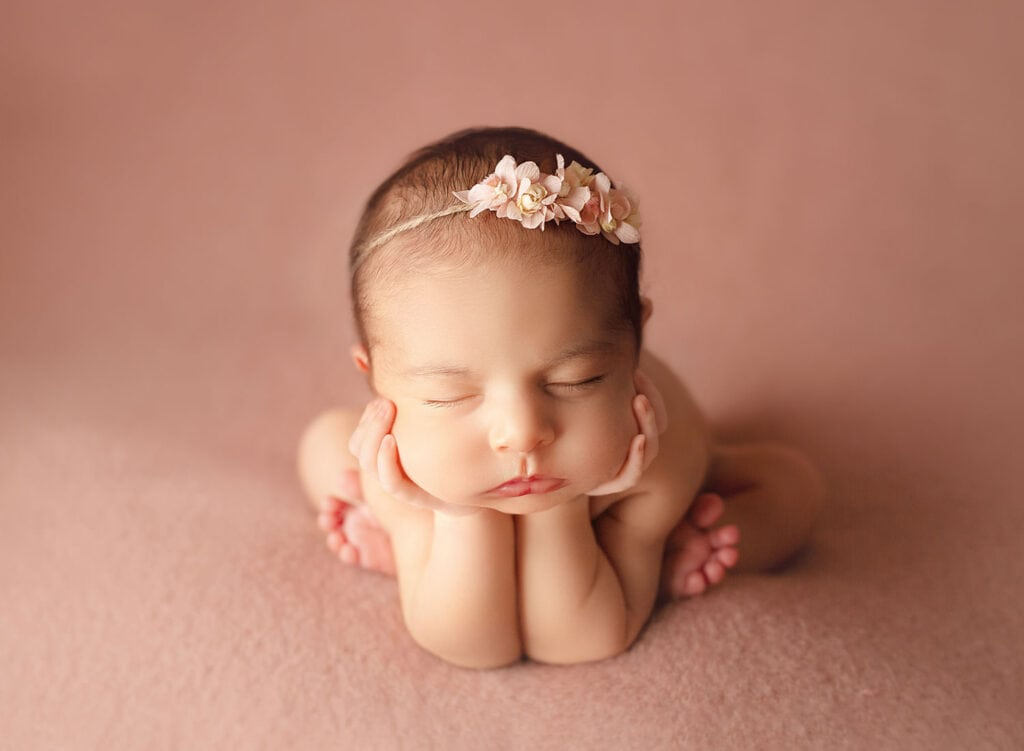 newborn girl in froggy pose on pink backdrop