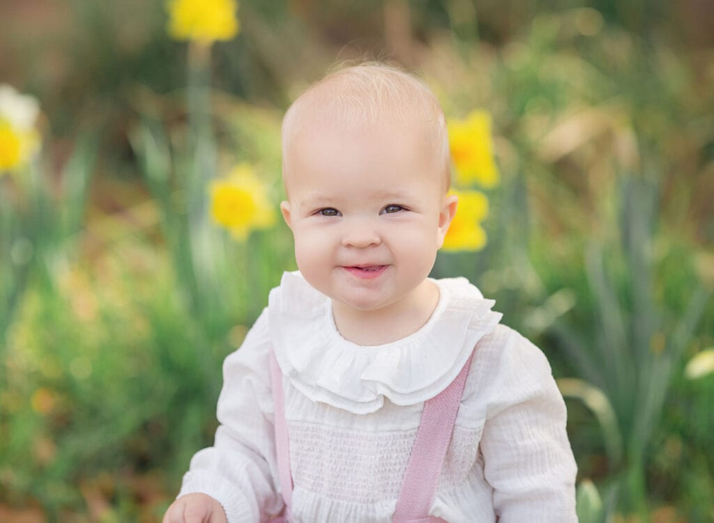 one year milestone session of baby girl in daffodils