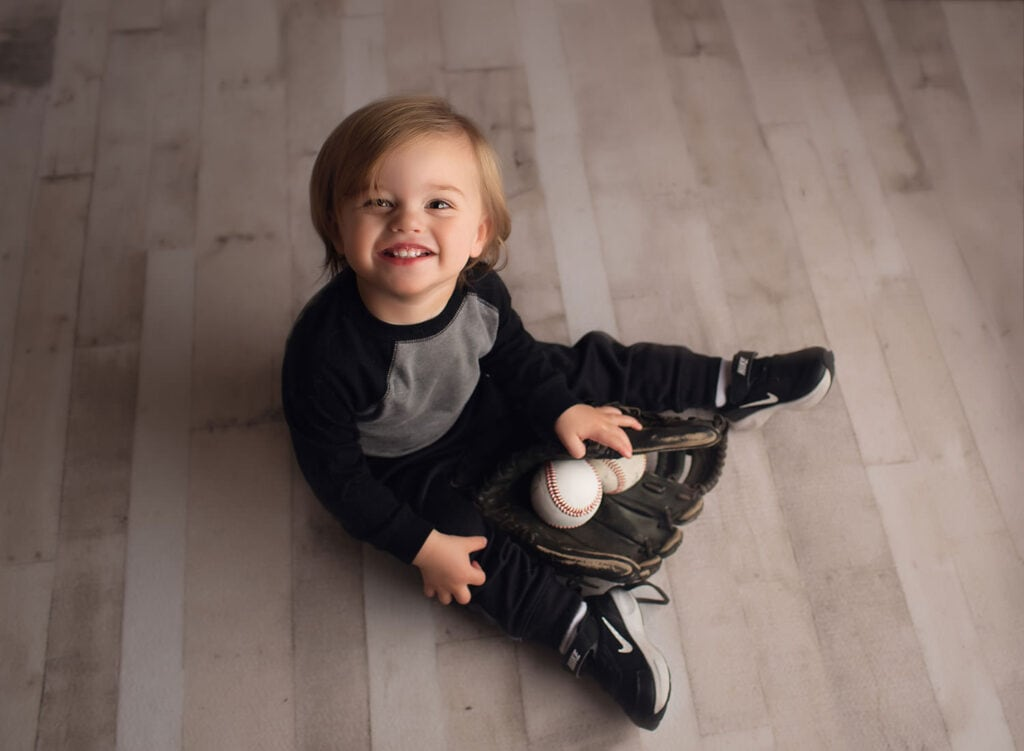one year old holding baseball and glove
