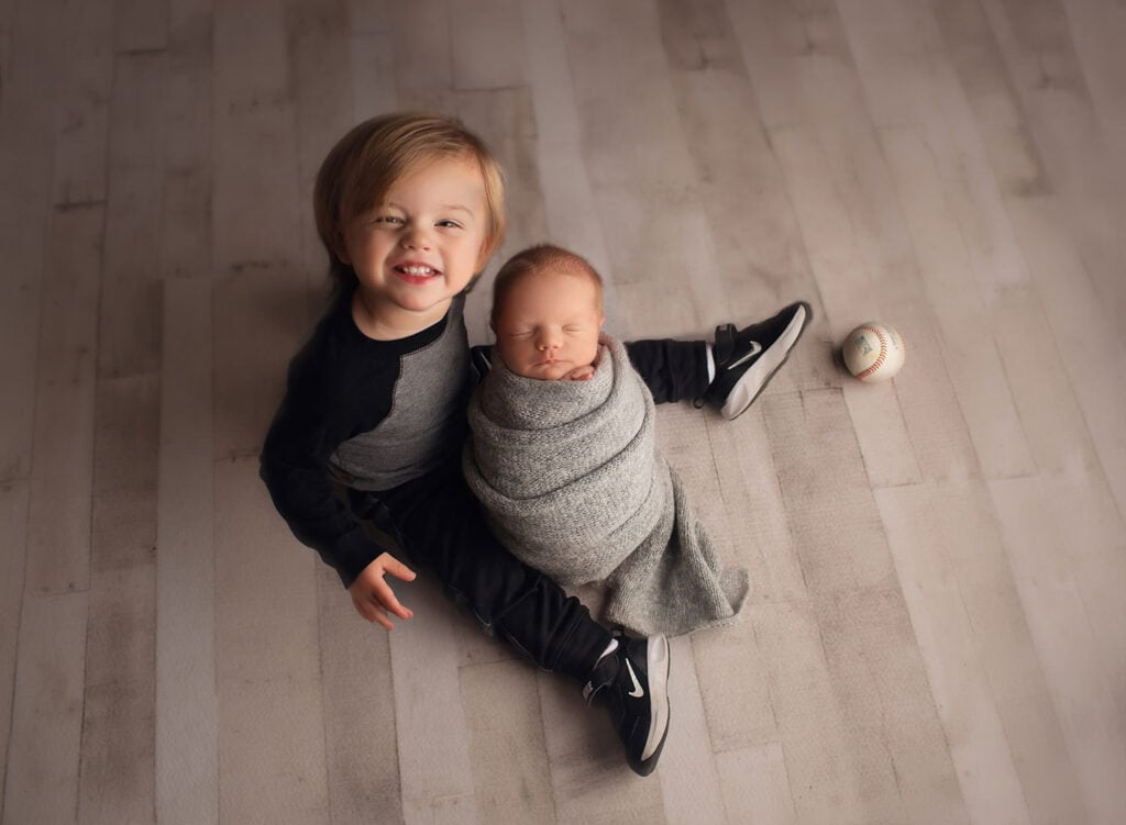 One year old holding newborn brother