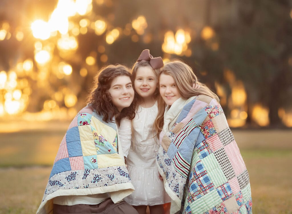 three sisters wrapped in vintage quilt