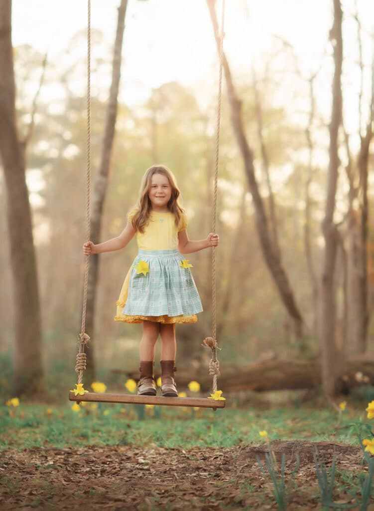 little girl in well dressed wolf yellow dress on swing with tulips in her pocket