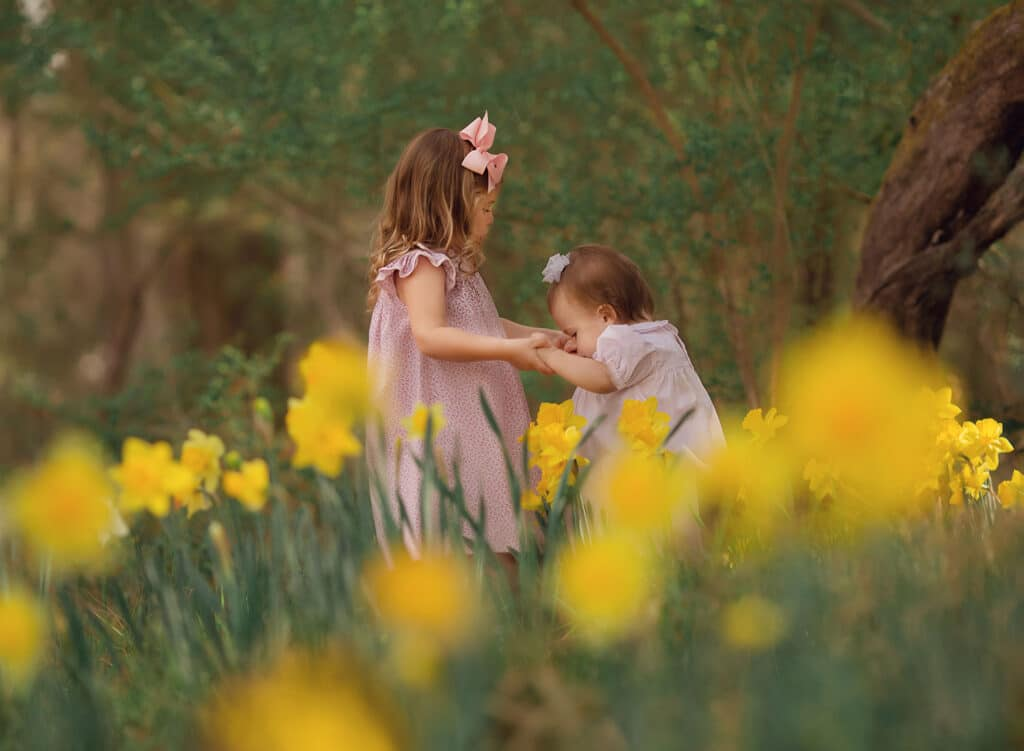 sisters holding hands in daffodil field