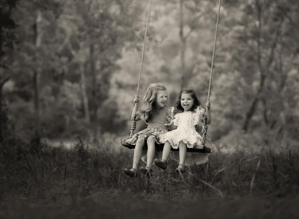 black and white photo of sisters on tree swing