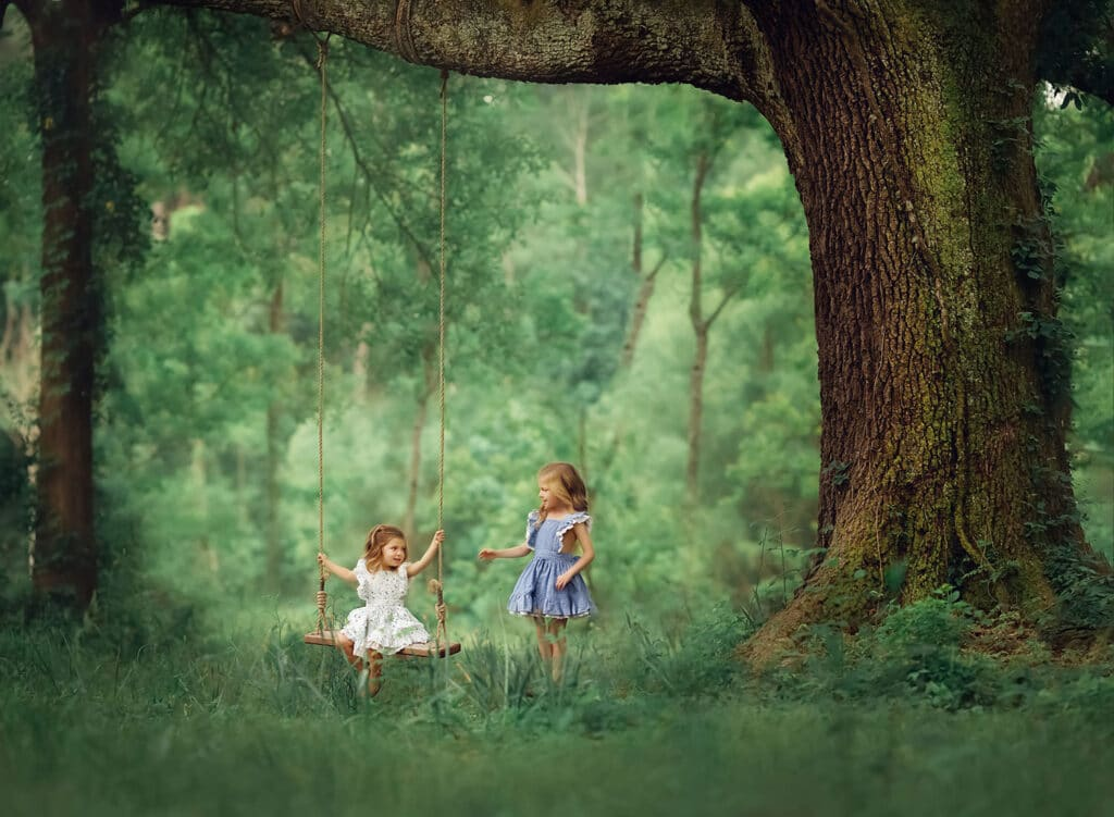 sisters playing under large oak tree