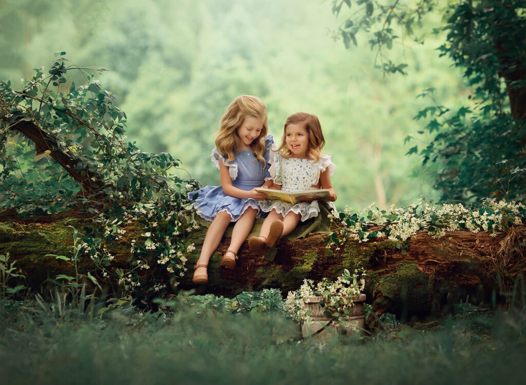 two girls on log reading book