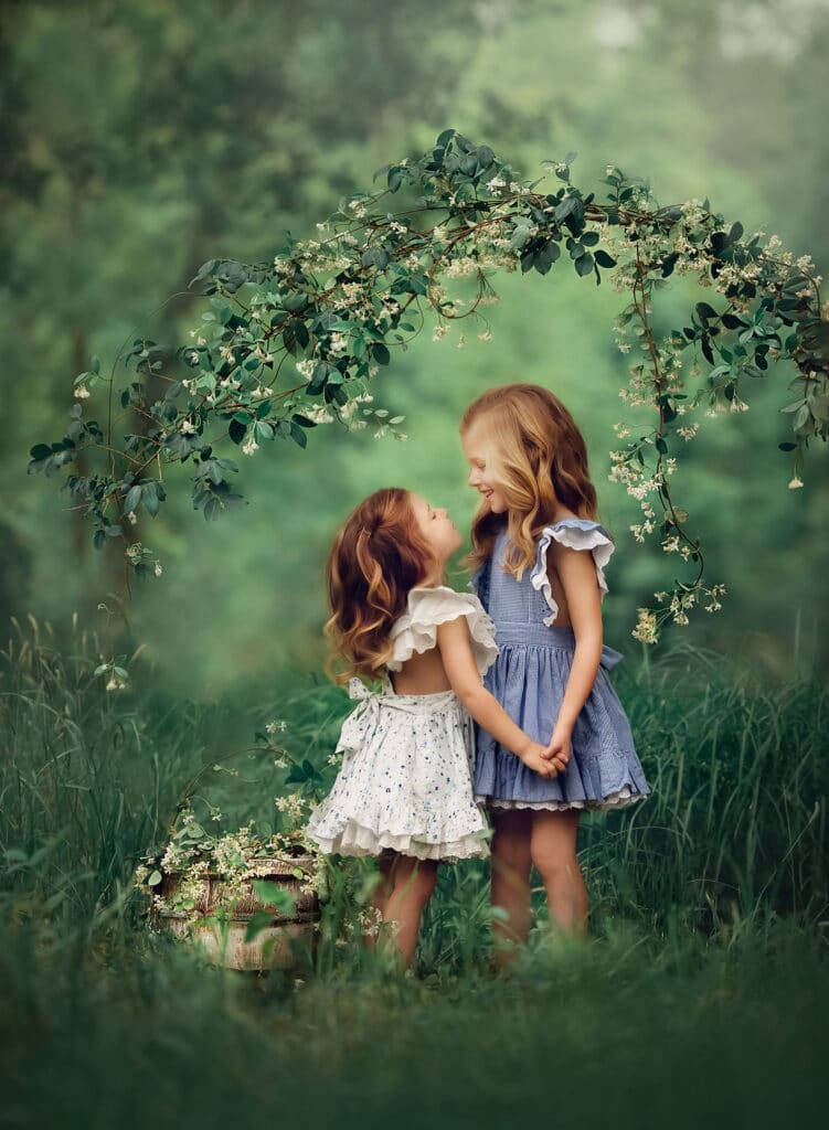fine art photo of two sisters under blooming jasmine