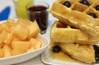 Belgian Style Waffles with Juice and Fruit on Table