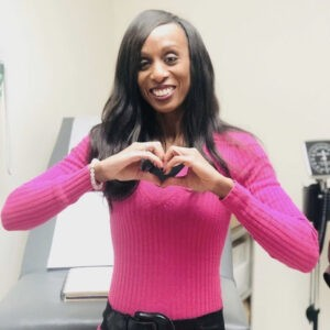 Dr Maggie Cadet Making the Heart Sign With Her Hands