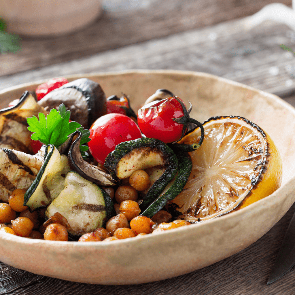 A bowl of vegetables including zucchini, cherry tomatoes and chickpeas