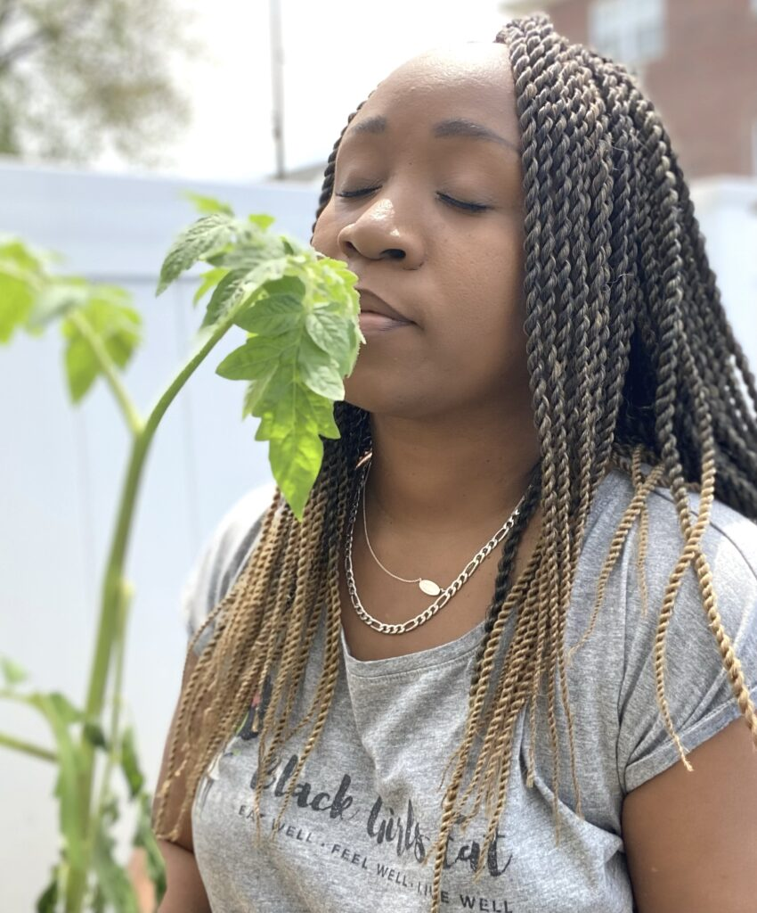 Woman smelling the scent of tomato plant