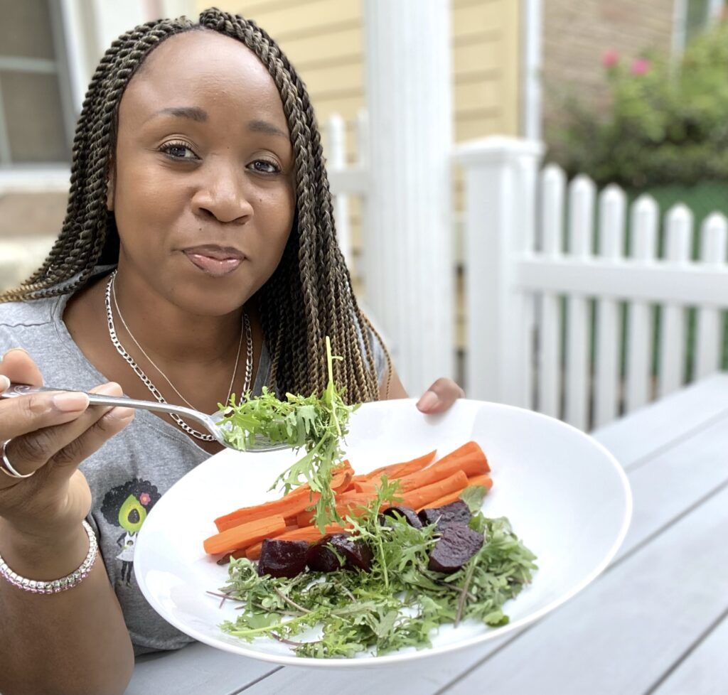 LA Dunn with a plate of carrots, beets and mixed spring greens from her garden