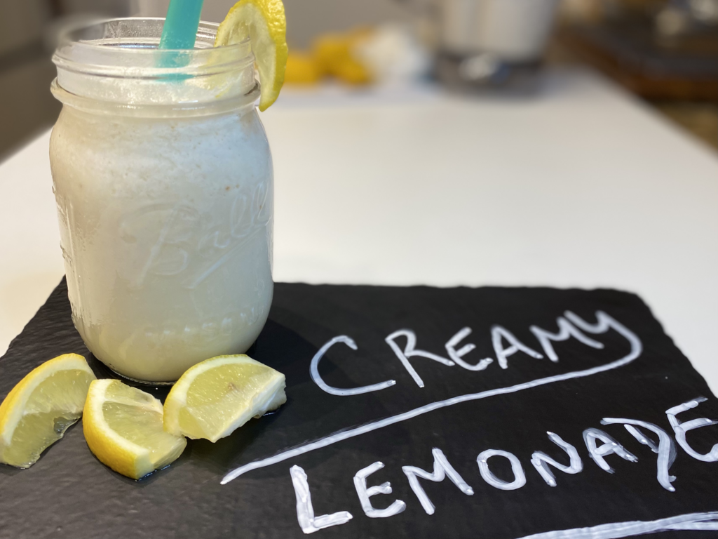 Creamy Lemonade in a mason jar on a chalk tablet with the words creamy lemonade written out.