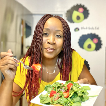 Woman holding a plate of watermelon strawberry basil salad