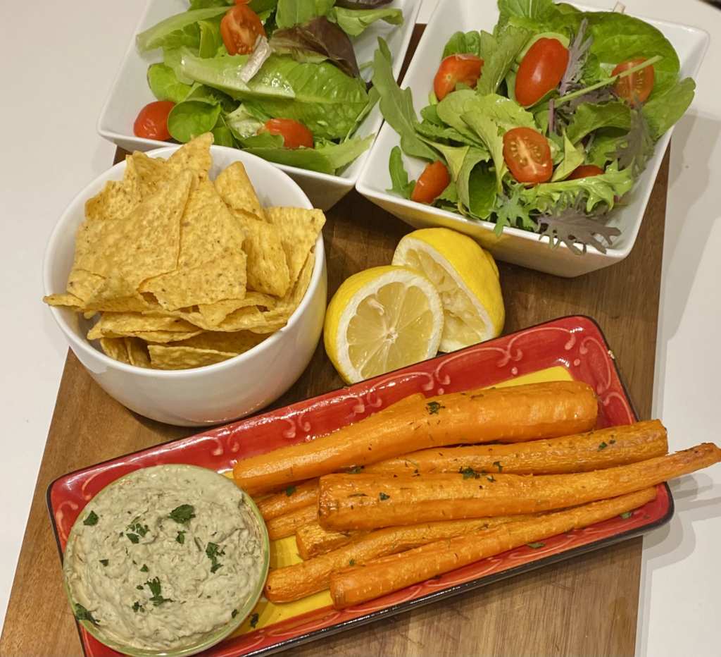 A tray of roasted carrots with hummus, chips and salad