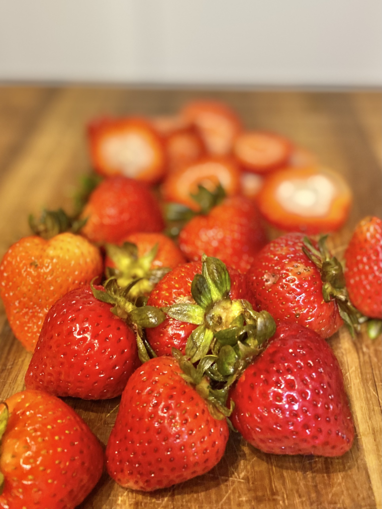 Loose strawberries on cutting board getting ready for the parfait.