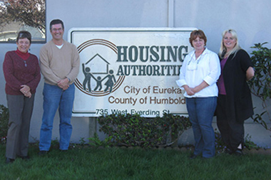 A group of individuals standing next to a Housing Authority sign