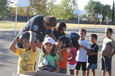 A group of children lined up with police officers putting helmets on them