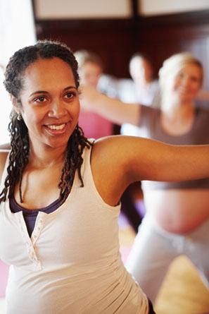 Pregnant women enjoying stretching during a prenatal fitness class