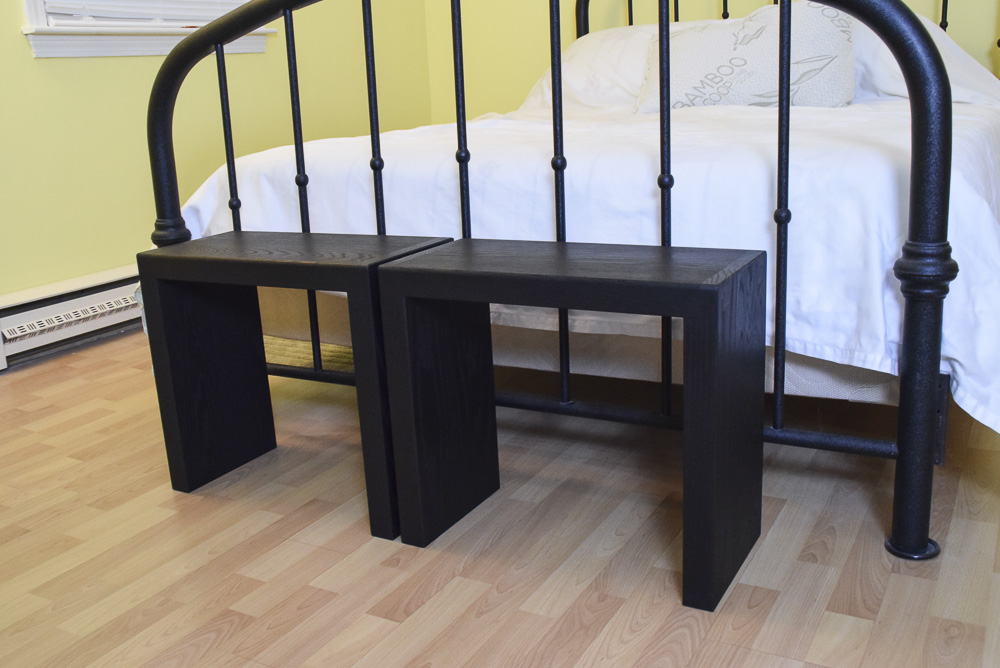 angled view of black oak sitting benches at end of bed