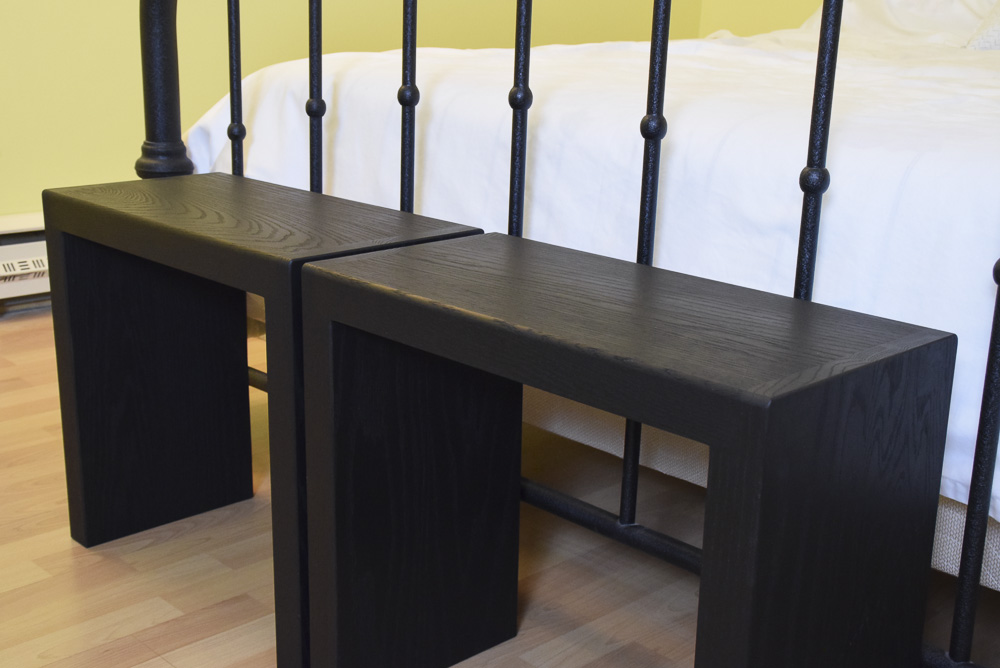 close up angled view of black oak sitting benches at end of bed