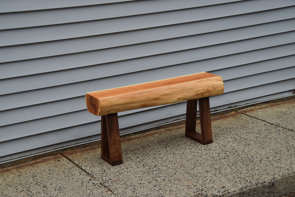 live edge yew bench with walnut legs viiewed above at an angle