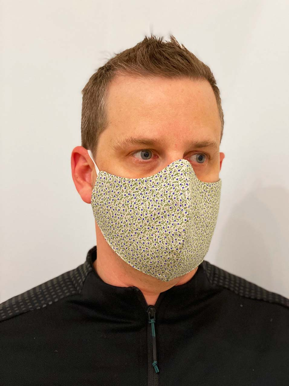 Designer reusable face mask with floral pattern worn by a man