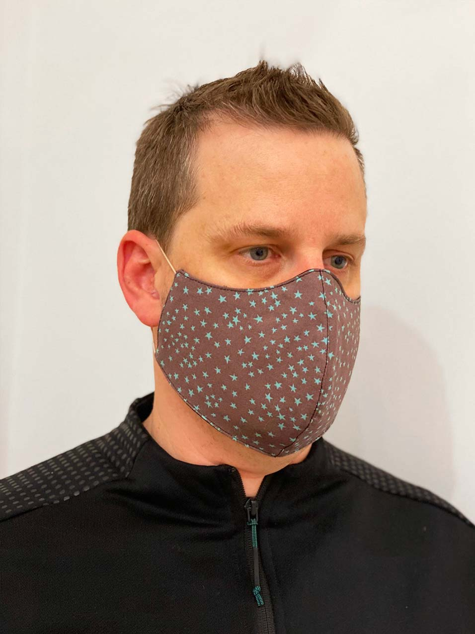 Designer reusable face mask with star pattern print worn by a man