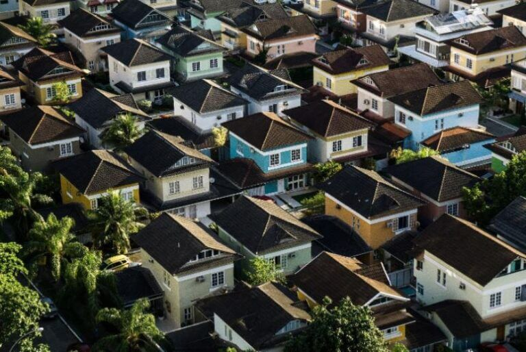 Linear housing area. Brown roofs and pastel bodies of the houses with a few trees around.