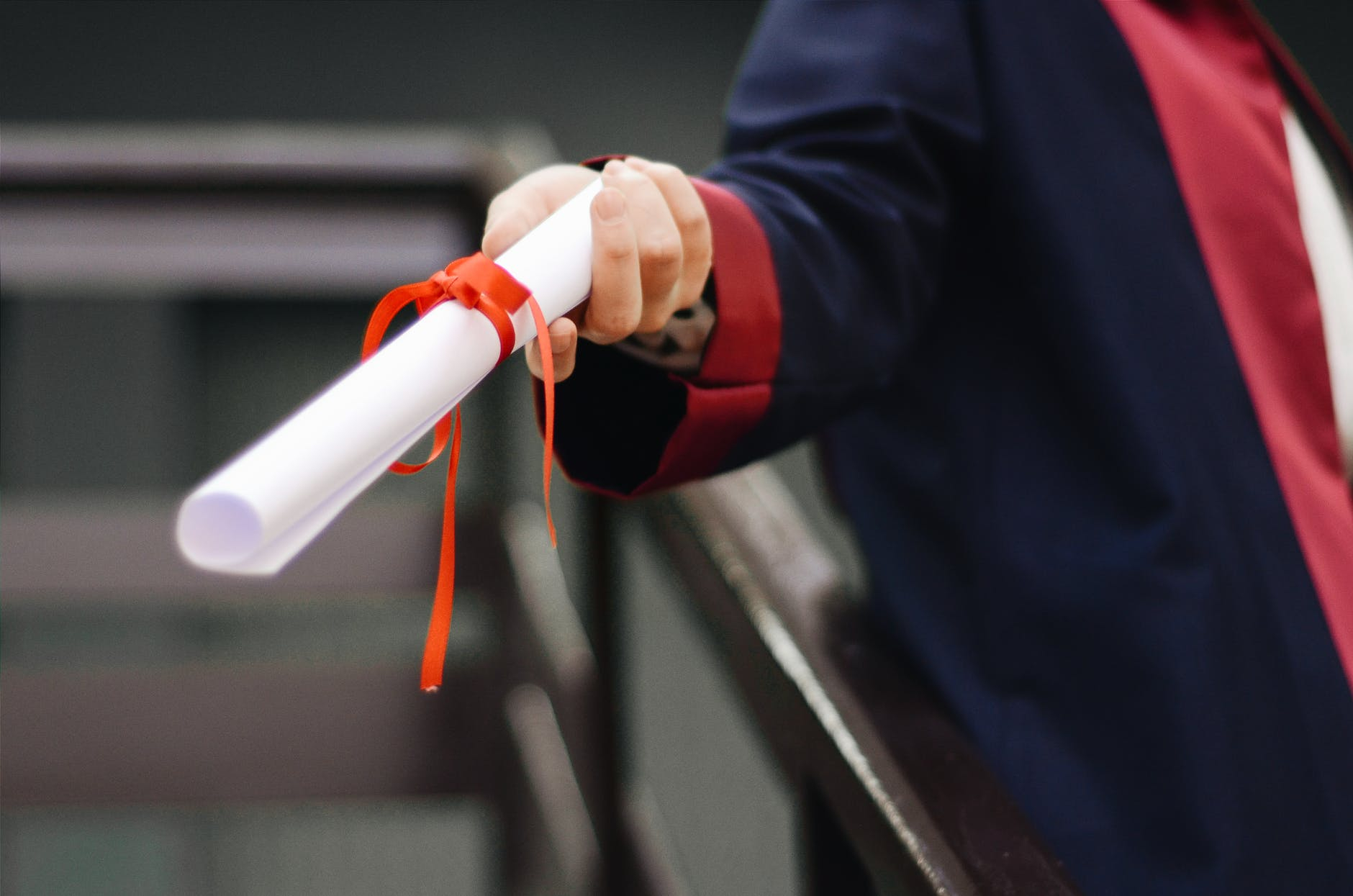 person holding white scroll - doctoral program