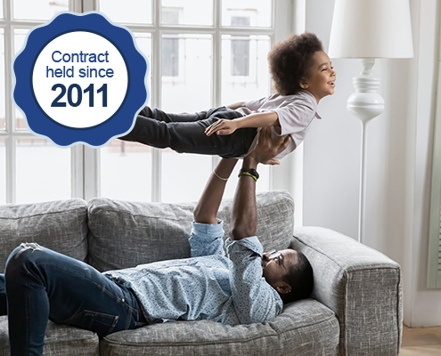 A Black father plays airplane with his son on a couch. A icon indicates WRMA has held this contract since 2011.