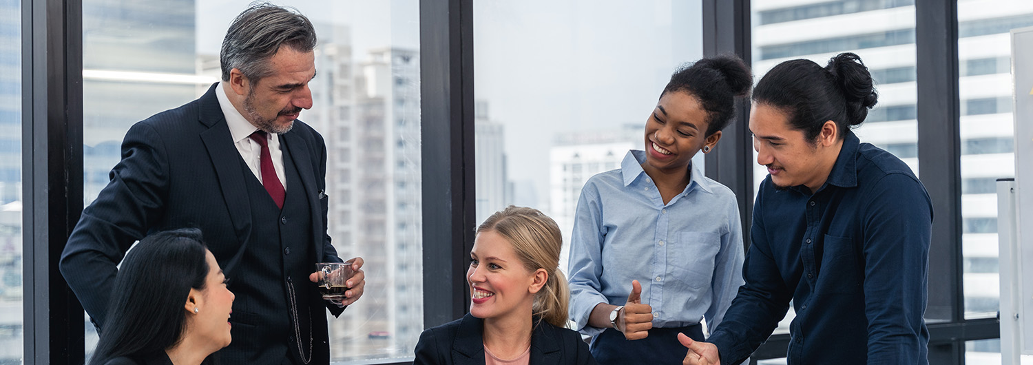 Corporate business team and manager in a meeting, celebrating a success with thumbs ups and smiles.