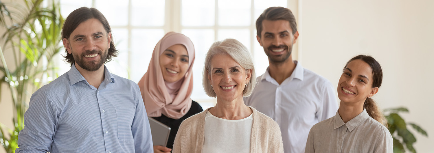Happy successful diverse team of professionals posing for portrait in a well-lit office..
