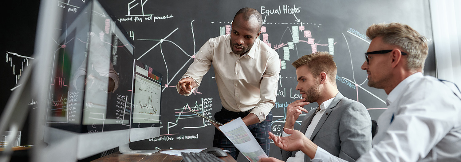 Three professional researchers comparing graphs, indexes and numbers on computer screens while working in the office. Blackboard full of charts in background.