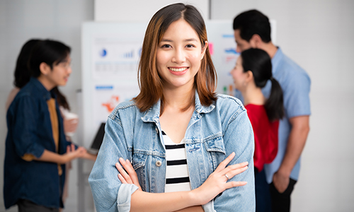 Confident young business woman in casual clothing smiles for a portrait while her team discusses data charts in the background.
