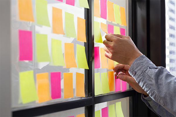 IT staff member sticks Post-It notes in an organized fashion on the wall to plan a project.