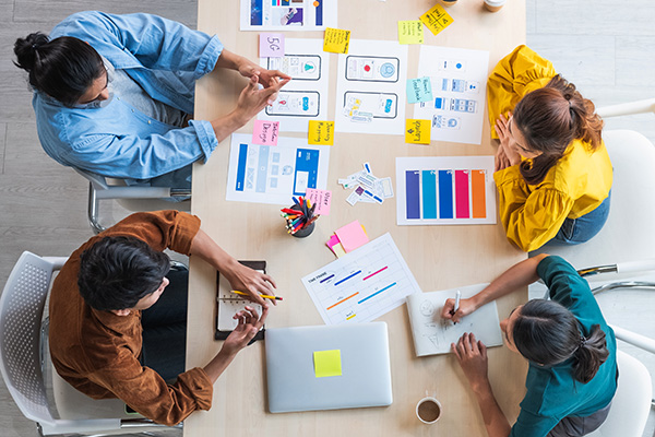 A top view image of a casual design team sharing mockups, color palettes, and sketches on a conference table.