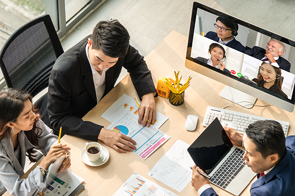 An overhead view of a team meeting, with three diverse staff at a conference table, which holds a computer monitor showing four more diverse staff members joining by videoconference.