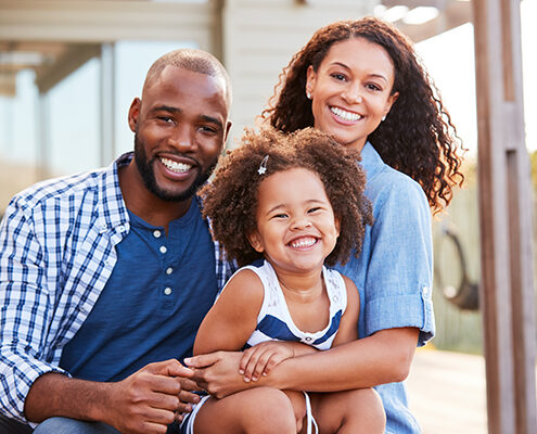 A happy Black family portrait, with a mother, father, and their young daughter.