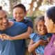 A happy Hispanic family with parents giving their two children piggyback rides.